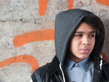 Young mixed race man , wearing a hood, stood against a graffiti wall Stock Photo - 16193525