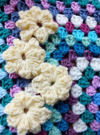 Four yellow crocheted flowers on a handmade blanket Stock Photo