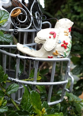 French style shabby chic metal bird cage with decorative vintage bird   hanging in garden  photo