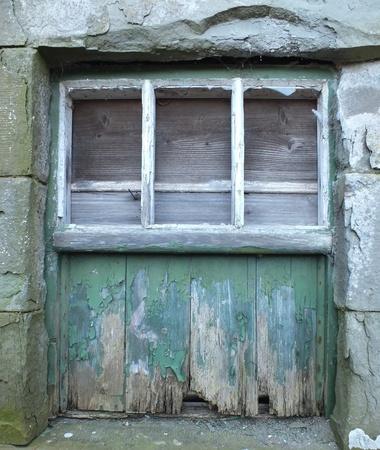 Old Grunge Window - broken glass, peeling wood , boarded up frame photo