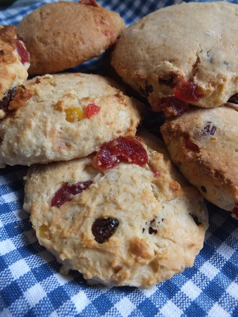 sultanas: Home made fruit rock cakes with cherries and sultanas, laying on a blue gingham cloth