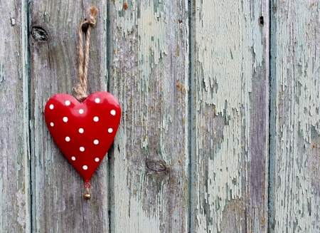 Red spotty heart on  of weathered wood, a rustic valentine image  photo