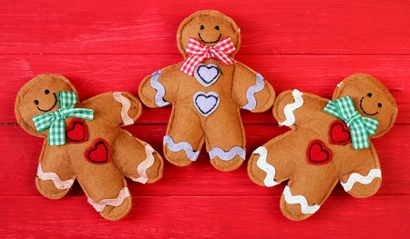 Three felt ginger bread men on red painted festive photo