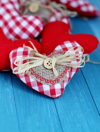 Shabby chic red and white gingham hearts with rustic decorations of buttons, straw and hessian, valentine and Christmas decorations   photo