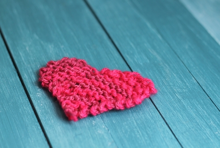 handmade pink  knitted heart shapes on blue wooden boards, shabby chic valentine gift photo