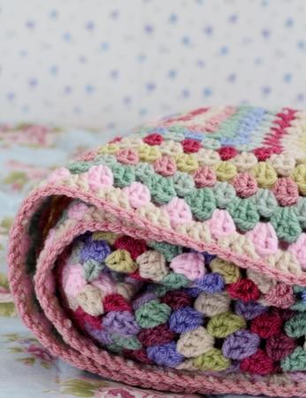 Pretty handmade crochet afghan blanket folded  on bed, made in yarn in shades of pink, cream, purple and green photo
