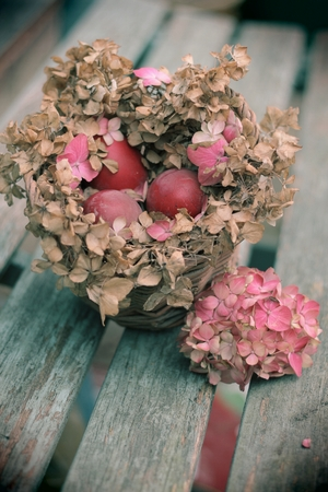 Instagram - esque image of a floral pink and brown hydrangea nest of dyed red eggs on a wooden bench, vintage Easter, photo