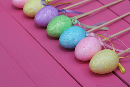Lined up Easter or party table decorations, egg shaped glittery, on pink painted boards  photo
