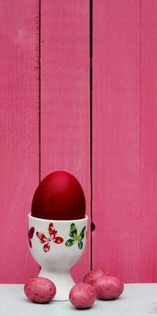 red dyed easter egg in a butterfly patterned  egg cup pink candy eggs background of painted pink wooden boards photo
