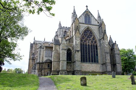 east end: Ripon Cathedral in Yorkshire UK, the east end of this historic church showing the graveyard , ancient spires, stained glass windows, medieval architectur Stock Photo