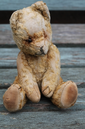 left behind: Old teddy bear sat on a vintage wooden bench , lost and lonely, left behind , retro , antique toy, childhood friend