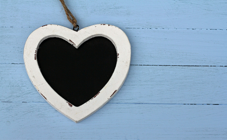 Heart shaped chalk board ,laying on blue painted floor boards  photo