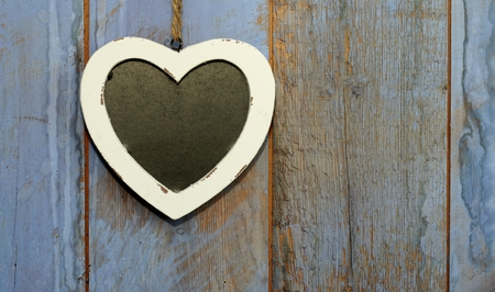Heart shaped shabby chic chalk board with white wooden frame hanging on rough wooden painted blue, purple barn doo photo