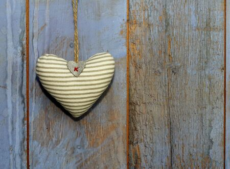 Cotton striped Heart shape shabby chic  with white wooden frame hanging on rough wooden painted blue, purple barn doo photo