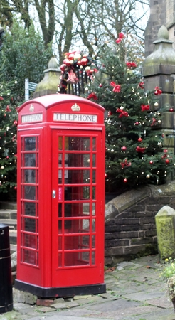 Traditional red British telephone box by the Hawarth church steps , decorated with a festive Christmas tree photo