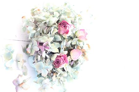 dried flower arrangement: Over exposed, pale image of dried blue hydrangea and pink rose buds, a romantic, ethereal flower arrangement on white wooden floorboards, wedding bouquet in pastel colors shabby chic Stock Photo