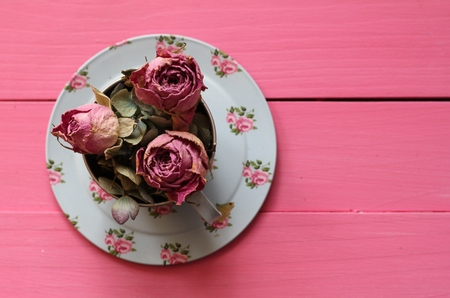 floorboards: Dried pink rose buds and pale dried hydrangea petals in a blue floral toy tin cup and saucer on pastel pink painted wooden floorboards