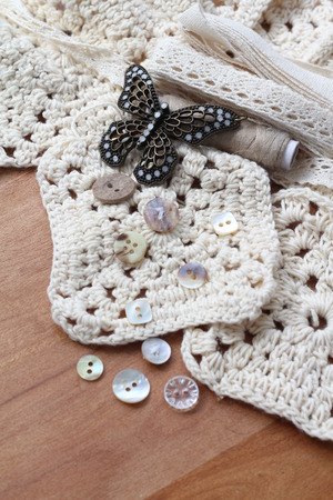craft materials: Cream crochet squares with soft cotton yarn, small pretty vintage buttons, beige thread, cream lace bundle collection of neutral coloured textile craft materials with metal decorative butterfly Stock Photo