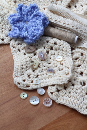 craft materials: Cream crochet squares with soft cotton yarn, small pretty vintage buttons, beige thread, cream lace bundle collection of neutral coloured textile craft materials with blue crochet flower