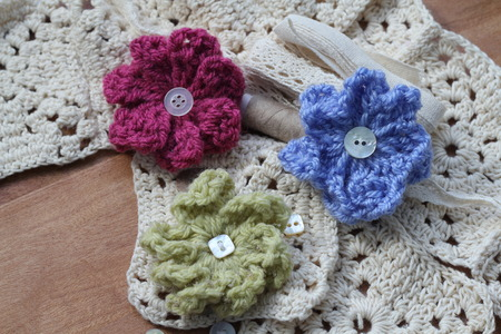craft materials: Cream crochet squares with soft cotton yarn, small pretty vintage buttons, beige thread, cream lace bundle collection of neutral coloured textile craft materials with three colourful crochet flowers Stock Photo