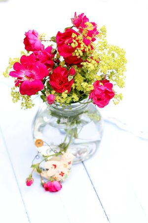 floral decoration: Over exposed Re-cycled glass jar with wild red roses and green Ladys Mantle flowers , with shabby chic bird ornament on pale blue wooden floorboards, summer outdoor wedding pretty arrangement,