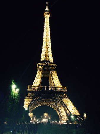 glow: Eiffel Tower at night , all lit up in Paris , main tourist attraction Stock Photo