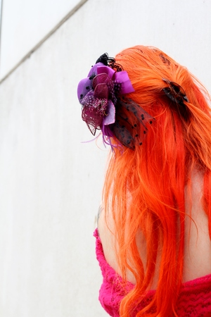 caucasion: Long dyed orange hair , alternative model back view, purple hair accessory and off shoulder pink dress, abstract image Stock Photo