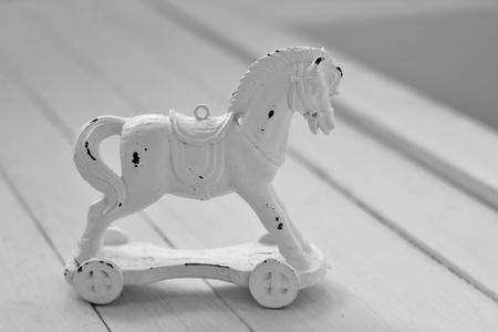 nostalgia: A white wooden vintage toy horse alone on white wooden floorboards, nostalgia,