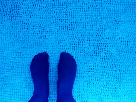 stocking feet: Royal Blue stocking feet on turquiose textured textile background, blue on blue simple composition
