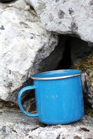 tin: Blue tin cup on dry stone wall, camping cup