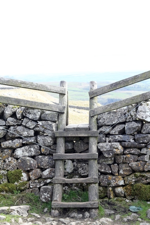 stile: Wooden Stile going over a dry stone wall on the Pennine Way in Malham Cove Yorkshire UK