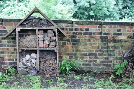 a house with a straw: Home for insects, a hand built enviromental house of wood, bricks, straw, stones and sticks by an old brick wall in green garden Stock Photo