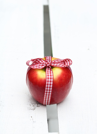 tied in: Gift of an apple , red apple tied in a gingham bow