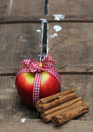 Red apple with gingham bow with cinnamon sticks on a vintage wooden crate , festive . Shallow depth of field