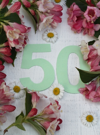 A pastel green paper cut number 50 surronded by pink spring blossom and daisies , birthday or anniversay card or invitation.