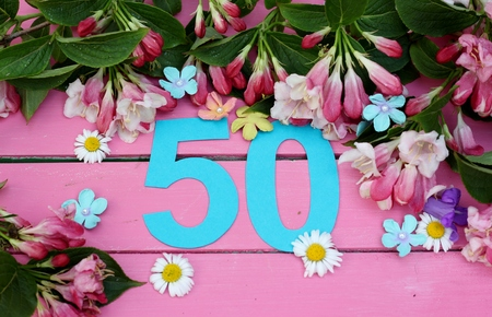 Number 50 in turquiose paper cut , surronded by spring flowers of daisies, blue bells, blossom and leaves on a bright pink painted wooden floor , image for birthday or anniversary card or invitations
