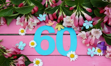 Number 60 in turquiose paper cut , surronded by spring flowers of daisies, blue bells, blossom and leaves on a bright pink painted wooden floor , image for birthday or anniversary card or invitations