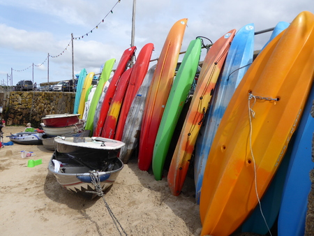 mousehole: Colurful plastic canoes lined up against the wall on the beach in Mousehole, often called the most beautiful village in the UK, Editorial