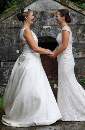 Beautiful brides holding hands and looking at each other, stood in front of an ancient stone building , wearing traditional white dresses for their same sex wedding