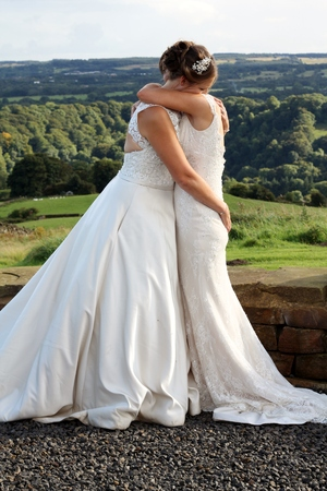 Brides holding each other after their wedding, both wearing traditional white dresses for their same sex marriage , hugging each other in the Yorkshire landscape