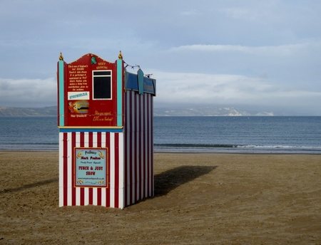 Weymouth, Dorset, UK, August 14th 2018 , a traditional British seaside childrens entertainment Punch and Judy theatre on an empty evening beach 新聞圖片