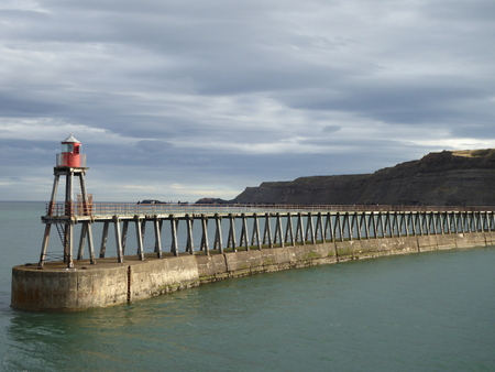 Jetty with a mini red light house at the end , in Whitby , North Yorkshire