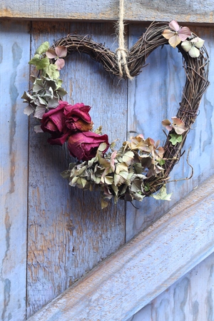 A hand made heart shaped dried flower wreath of roses and hydrangea hanging on a blue painted barn door