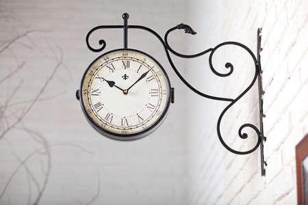 Black vintage watch with Roman numerals in the white studio interior