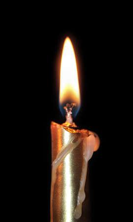 Close up of aureate burning candle on black background