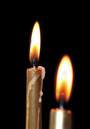 Close up of two aureate burning candles on black background Stock Photo