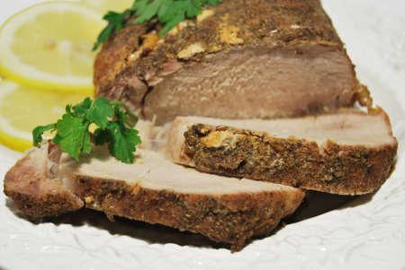 Close up roast pork with lemon and parsley on a plate