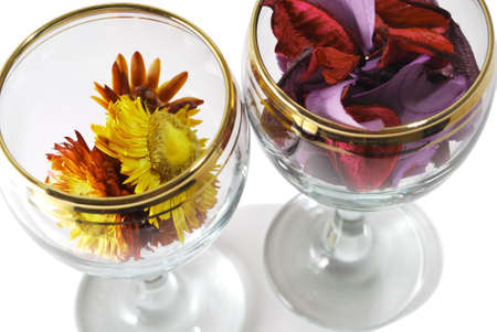 Closeup photo of two isolated  glasses with pressed flowers on a white background