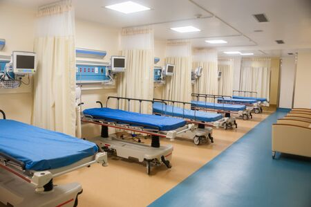 Emergency room with several blue hospital beds