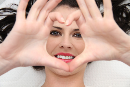 Beautiful young woman with blue eyes making heart of fingers